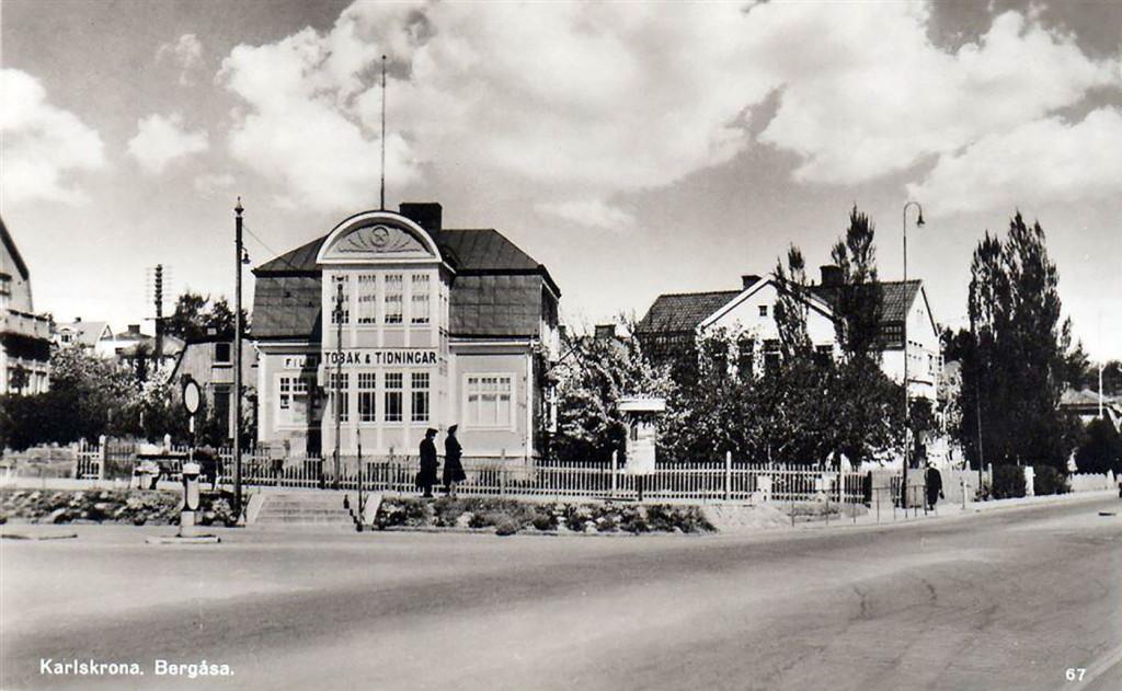 Vykortet visar systrarna Glans tobaks- och pappershandel där senare Sparbanken flyttade in i huset och idag är det en tapetserarverkstad. Bilden är från början av 1950-talet just efter att Karlskrona spårvägar lagts ned. De hade sin ändhållplats just framför huset, men spårvägen ersattes 1949 av bussar och ringlinjerna 11 och 12.