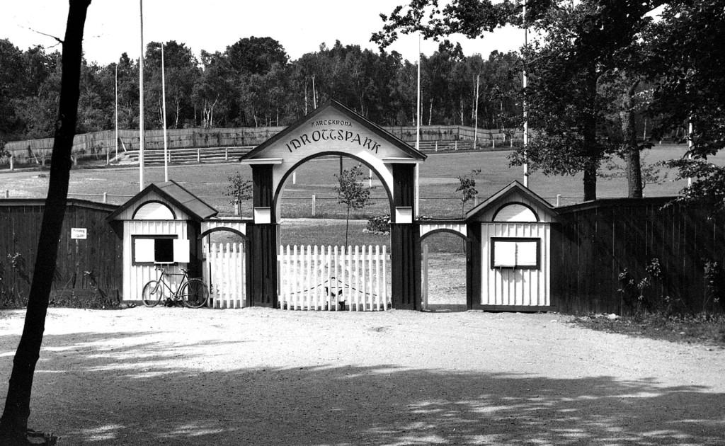Bilden visar Karlskrona Idrottspark på Västra Mark och den dåvarande entrén till anläggningen. Bilden bör vara tagen några år efter den högtidliga invigningen den 13 september 1925.